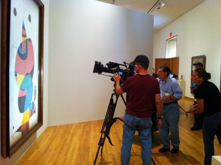 Mike Burke, director of photography (left) for UNC-TV, films Joan Miró's 1966/1973 oil on canvas painting, Woman, Bird and Star (Homage to Pablo Picasso), which is more than 8 feet tall. Executive Producer/Director Scott Davis looks on with Debora O'Neill, associate producer. Photo by Wendy Hower.