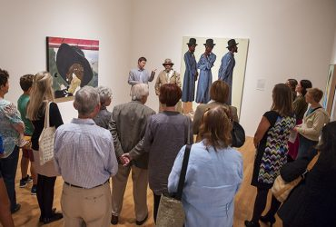 Visitors enjoy a gallery talk led by Chief Curator Trevor Schoonmaker (back left) and artist Barkley L. Hendricks (back right), within Reality of My Surroundings. Photo by J Caldwell.