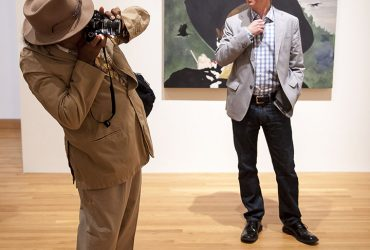 Artist Barkley L. Hendricks takes a photo of Chief Curator Trevor Schoonmaker in front of a painting by Noah Adams, within Reality of My Surroundings. Photo by J Caldwell.