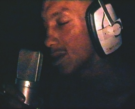 "This early work demonstrates McQueen's improvisational and reductive approach to video making, using a hand-held camera, restricted lighting, and limited editing. It captures a close-up rehearsal by the experimental ""trip-hop"" musician and producer Tricky (Adrian Thaws) as he practices a song in his dimly lit studio. Recorded over four days in this small space, the video presents an intimate portrayal of a raw creative act. McQueen noted, ""It's a rare moment that you see an artist close up gearing himself up for a vocal performance in such a visual way. In effect, a moment not for camera is caught."""