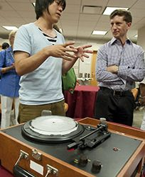 "Japanese artist Lyota Yagi, visiting for the opening of The Record, plays a record made of ice, of the songs ""Clair de Lune"" and ""Moon River,"" as University of North Carolina at Chapel Hill professor Mark Katz looks on. The music warbles and disintegrates as the grooves in the record melt. Yagi's 9-minute video, Vinyl (Clair de Lune + Moon River), is part of The Record. Katz contributed an essay to the exhibition catalogue. Photo by J Caldwell."
