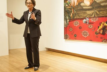 Nancy A. Nasher, chair of the museum's national Board of Advisors, chats in the gallery alongside Barkley's painting, Take All the Time You Need (Adrienne Hawkins), part of the museum's collection. Photo by J Caldwell.