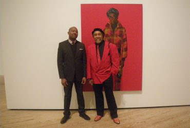 Dr. Kenneth Montague (left) poses with Barkley L. Hendricks in front of Blood (Donald Formey), a painting created by Barkley in 1975, which Montague purchased for his contemporary collection, The Wedge Collection. Photo by J Caldwell.