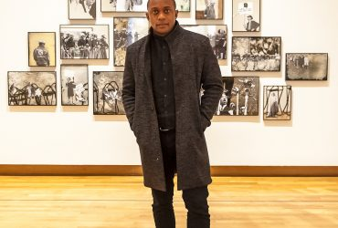 Hank Willis Thomas poses with his work, Ain't Gonna Let Nobody Turn Us Around, commissioned by the Nasher Museum and part of the museum's collection. Photo by J Caldwell.