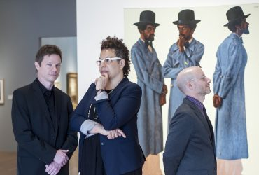 Sandra Jackson-Dumont, the Frederick P. and Sandra P. Rose Chairman of Education at the Metropolitan Museum of Art (center), poses with museum curators Trevor Schoonmaker and Marshall Price in front of a painting by Barkley L. Hendricks, Bahsir (Robert Gowens). Photo by J Caldwell.