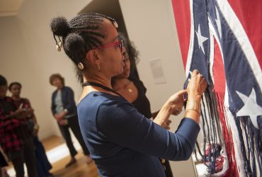 Artist Sonya Clark performs Unraveling in the gallery, at the opening of Southern Accent: Seeking the American South in Contemporary Art. Photo by J Caldwell.