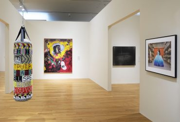 This installation view of Southern Accent features a work by Jeffrey Gibson, I PUT A SPELL ON YOU, on the left, with (left to right) works by Robert Colescott and Diego Camposeco in the gallery. Photo by Peter Paul Geoffrion.
