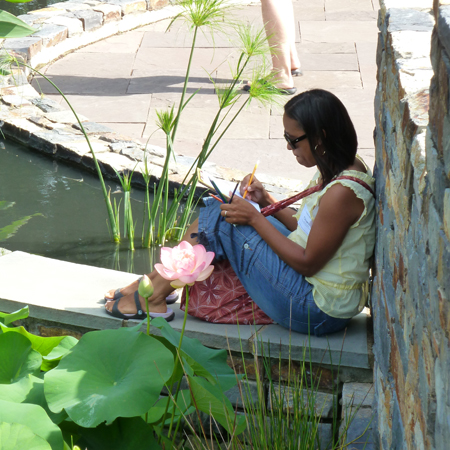 A Durham teacher during a Nasher Teacher Workshop enjoys drawing by the pond at Duke Gardens.