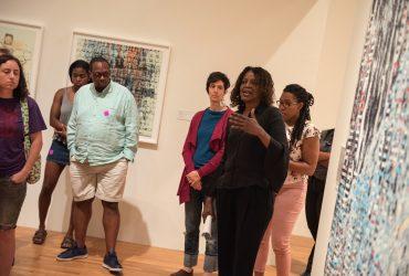 Mark Anthony Neal, Chair of the Duke University Department of African & African American Studies, looks on as Duke Professor Thavolia Glymph talks about artist Mark Bradford