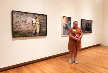 Artist Genevieve Gaignard poses with her photographs in People Get Ready