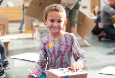 A young visitor works on her cardboard city at Free Family Day. Photo by J Caldwell.
