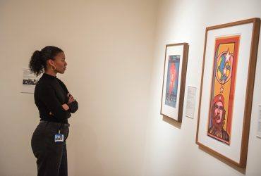 Adria Gunter takes a deeper look at works within Pop América during the opening event. Photo by J Caldwell.