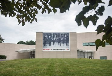 A RESIST COVID / TAKE 6! banner at the Nasher Museum, facing Anderson Street. Courtesy of Carrie Mae Weems. Photo by J Caldwell.