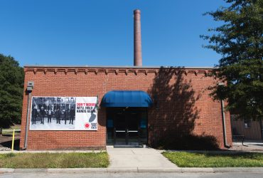 A RESIST COVID / TAKE 6! banner at the Carpentry Shop, home of the MFA / EDA program, adjacent to Smith Warehouse. Courtesy of Carrie Mae Weems. Photo by J Caldwell.